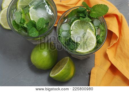 Two Glasses With Mohito And Ice With Lime Citrus Fruits. Orange Napkin