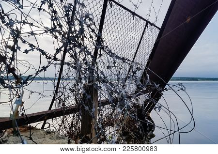 Barbed Wire On The Background Of The Sea. The Barbed Wire Razor Is Random At Random. Abstract Pictur
