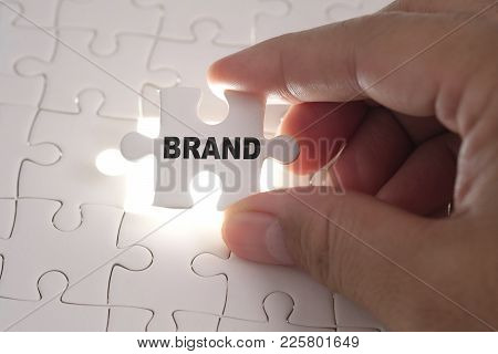 Brand Word On Jigsaw Puzzle. Businessman Hands Holding White Puzzle Business Concept.