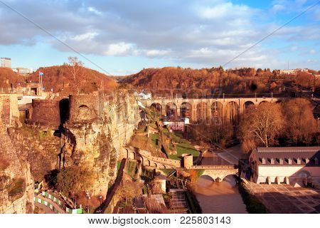 a view of the Alzette River as it passes through the Grund Quarter in Luxembourg City, Luxembourg, highlighting the remains of the ancient fortress in the Bock promontory on the left