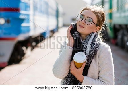 Traveling Tips. Tourism Vacation Journey. Cosy Clothes And Hot Coffe To Stay Warm. Woman At A Railwa