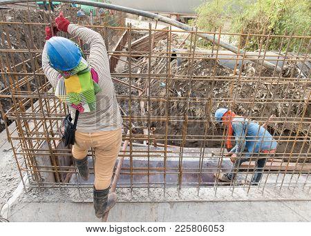 Construction Worker Assembling Steel Rebar At Construction Site.