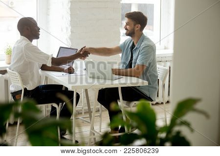 Black And White Entrepreneurs Shaking Hands Sitting At Office Desk, Satisfied Multi-ethnic Casual Bu