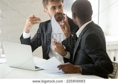 Multiracial African And Caucasian Partners Arguing About Contract Fraud, Dissatisfied Diverse Busine