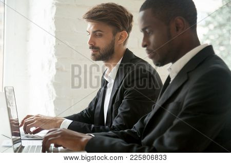Sneaky Curious Caucasian Businessman Secretly Looking At Laptop Screen Of African Colleague Stealing