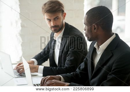 Caucasian Businessman Looking At African Business Rival With Hate Dislike Envy, Diverse Competitors