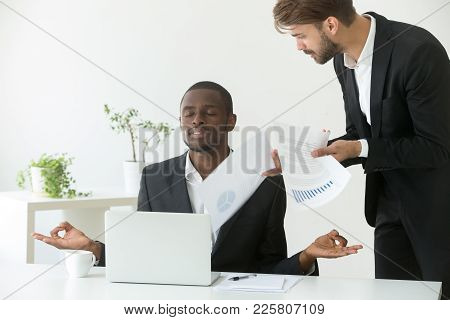 Calm Mindful African American Businessman Practicing Yoga At Workplace Ignoring Angry Bad Boss, Blac