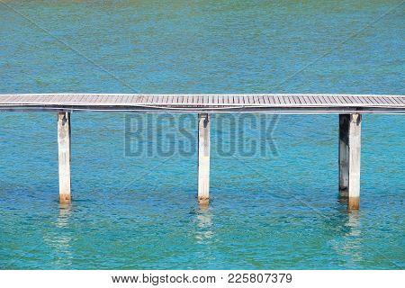 Wooden Walkway Bridge Over The Sea Water With Triple Piers