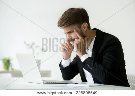Tired Businessman Squinting Eyes Looking At Laptop Screen Trying To Focus Concentrate, Office Employ