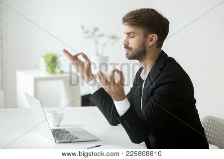 Successful Businessman Wearing Suit Meditating In Office For Concentration Development, Calm Mindful