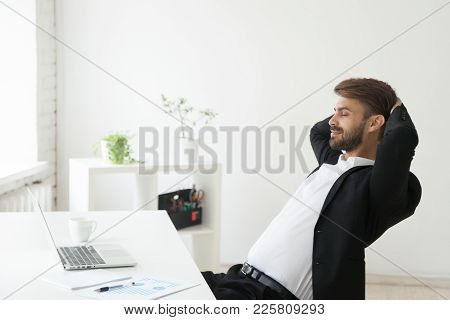 Relaxed Successful Businessman In Suit Enjoying Office Break Holding Hands Behind Head At Workplace,