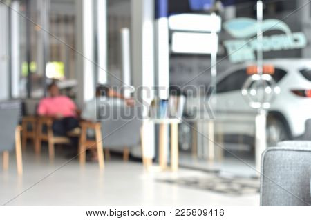Men Who Are Customers Sitting On Sofa In The Guest Lounge Waiting For A Car Inspection At The Car Sh