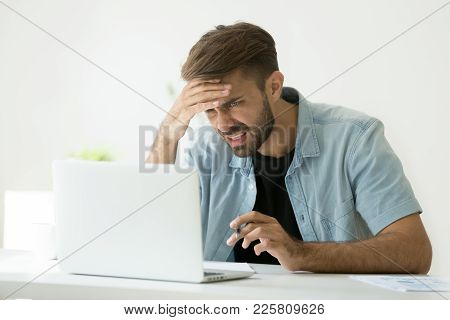 Confused Young Man Frustrated By Online Problem Looking At Laptop Screen, Worker Troubled Doing Hard