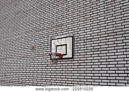An Old Basketball Hoop Attached To A Black And White Brick Wall In The Small Rural Town Of Oulainen