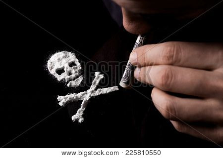 Drug Dependence Kills. Junkie Man Sniffing A Line Of Cocaine In The Shape Of A Skull Through A Dolla