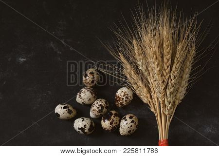 On A Black Background, Yellow Wheat And Ripe Quail Eggs.