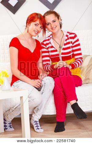 Two Happy Girlfriends Sitting On Sofa At Living Room