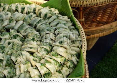 Many Of Fresh Chinese Chives Dumplings Snack On Green Banana Leaf In Rattan Basket