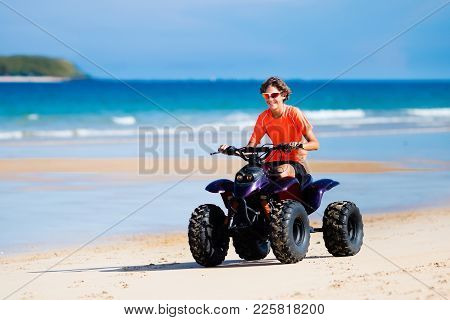 Teenager Riding Quad Bike On Tropical Beach. Active Teen Age Boy On Quadricycle. All-terrain Vehicle