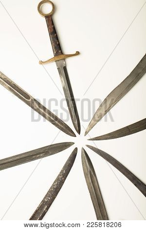 Isolated Old Dagger With Assorted Blades Of Weapons All Pointing To A Central Point With Copy Space