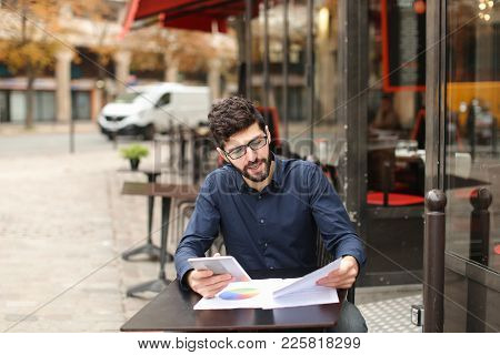 Skilled Financial Analyst Chatting With Tablet At Cafe Table And Smiling. Resting Young Man Using Mo