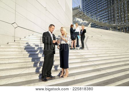 Boss Keeping Tablet And Speaking With Blonde Secretary On Stairs With Biz Partners In Background. Co