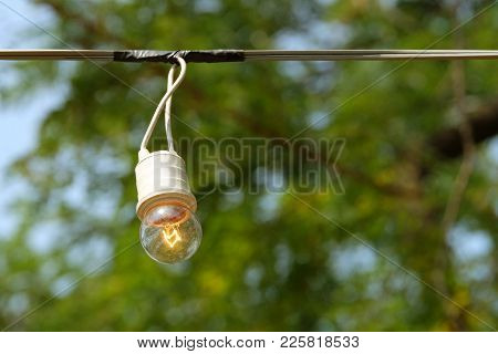 Vintage Filament Lamp With The Glow Tungsten Inside Hanging From The Electric Line On Blurry Outdoor