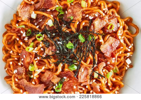 Korean Hot And Spicy Instant Noodle In Black Bowl. Spicy Noodles Topped With Bacon, Sesame, Seaweed
