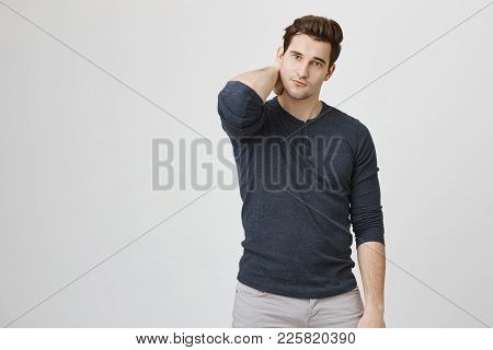 Portrait Of Slim Handsome Man Scratching His Neck And Looking At Camera Feeling Unconfident, Isolate