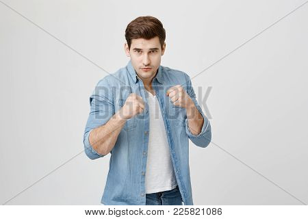 Defense And Protection Concept. Strong Man Wearing Denim Shirt With Stylish Haircut Having Serious A
