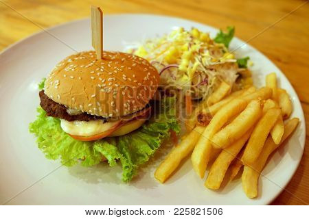 Hamburger With Salad And French Fries Side Dish In White Plate On Wooden Table