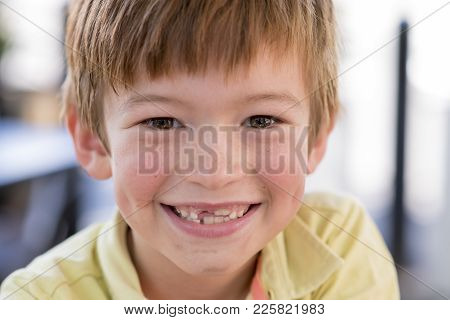 Close Up Headshot Portrait Of Young Little 7 Or 8 Years Old Boy With Sweet Funny Teeth Smiling Happy