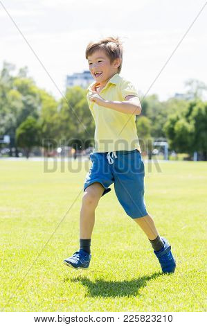 Vertical Portrait Of Young Little Kid 7 Or 8 Years Old Enjoying Happy Running Excited And Free At Gr