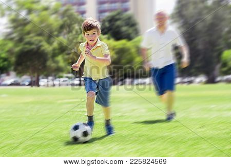 Young Happy Father And Excited 7 Or 8 Years Old Son Playing Together Soccer Football On City Park Ga