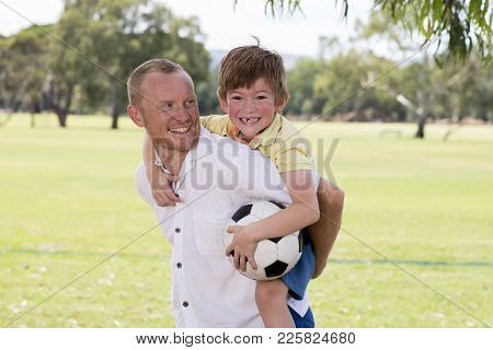 Young Happy Father Carrying On His Back Excited 7 Or 8 Years Old Son Playing Together Soccer Footbal