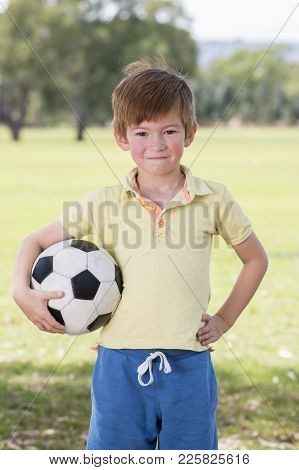 Young Little Kid 7 Or 8 Years Old Enjoying Happy Playing Football Soccer At Grass City Park Field Po