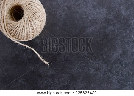 Ball Of Twine From Above, Unwinding On Grey Background