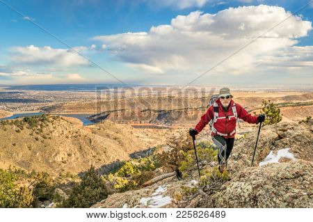 a mature backpacker with trekking poles on a mountain ridge in winter scenery - Horsetooth Rock trail above Fort Collins in northern Colorado