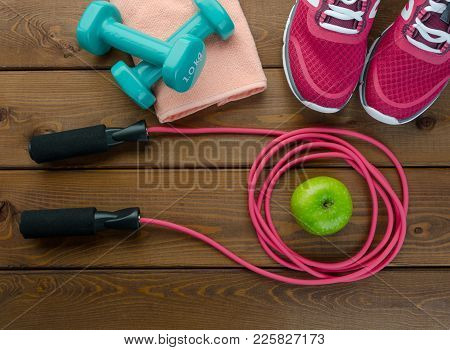 Fitness Concept With Sneakers Bottle Of Water Apple And Skipping Rope On Wooden Table Background