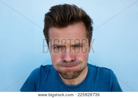 Humorous Emotional Portrait Of Grimacing Young Man. He Is Blowing His Cheeks. He Is Very Angry But T