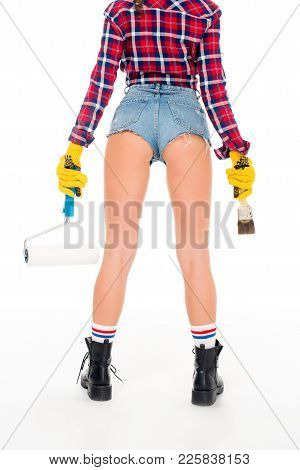 Rear View Of Sexy Girl In Gloves Holding Painting Roller And Brash, Isolated On White