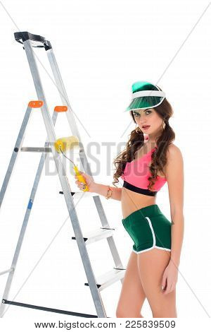 Sexy Girl In Visor Holding Painting Roller And Standing Near Ladder, Isolated On White