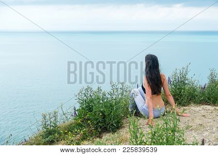 Young Beautiful Woman 25-30 Years Sitting On The Mountain And Looks At Sea, Back View. Summer Evenin