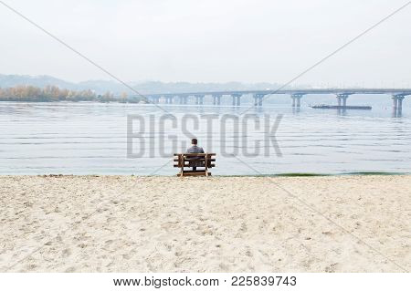 One Man Is Sitting On A Bench At River Bank And Looking Down On A Water.