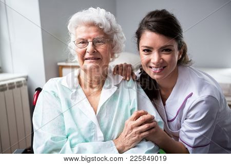 Smiling Nurse And Old Woman Patient At Wheelchair