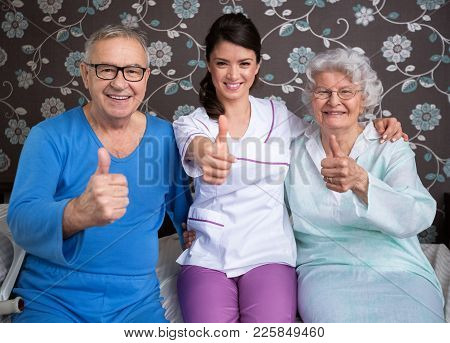 Smiling Satisfied Elderly People With Nurse