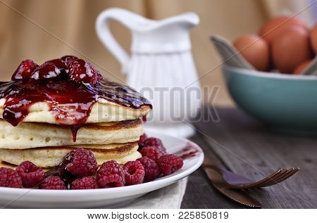 Delicious Homemade Golden Pancakes With Fresh Raspberries And Raspberry Syrup. Extreme Shallow Depth