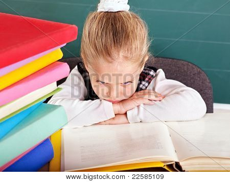 Happy schoolchild in classroom near blackboard.