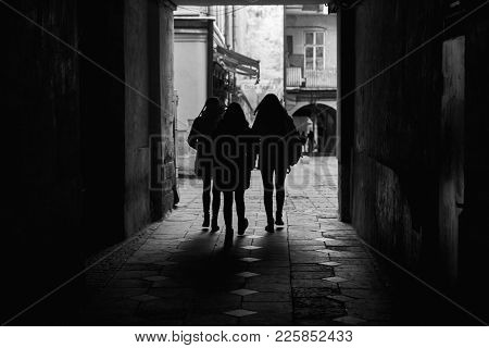 Lviv, Ukraine - November, 2017. Silhouettes Of People Walking Through A Tunnel Of An Ancient City. B