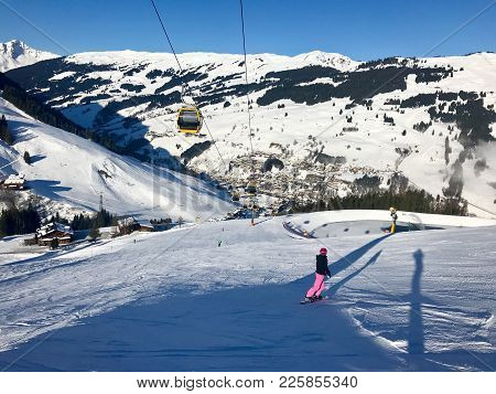 Female Snowboarder Boarding Over The Piste With View Downwards Into The Valley Of Saalbach-hintergle
